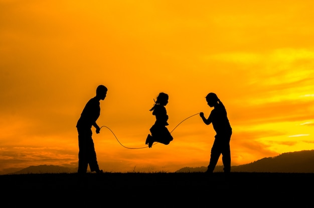 Silhouette of children playing jump rope.
