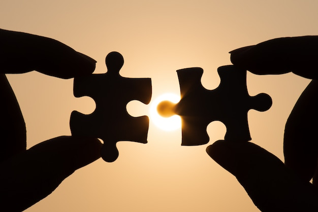 Silhouette of closeup woman's hand connecting a piece of jigsaw puzzle