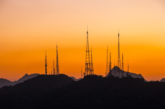 Silhouette of communication antennas on the sumare hill in rio de janeiro, brazil.