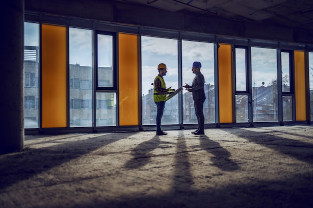 Silhouette of construction worker and architect standing near window in future business center and talking about realization of the project.