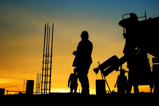 Silhouette construction worker concrete pouring during commercial concreting floors