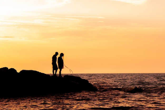 Silhouette of couple on the beach with a beautiful sunset