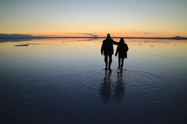 Silhouette of a couple exploring the incredible mirror effect of uyuni salt flats, bolivia