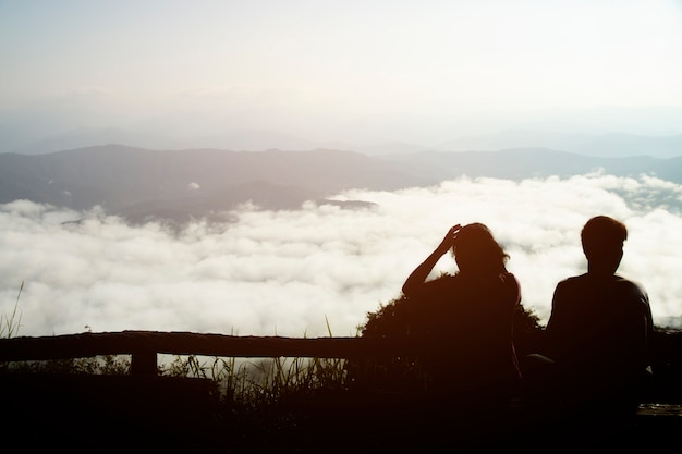 Silhouette of couple on a high mountain valley with sunrise in the morning.