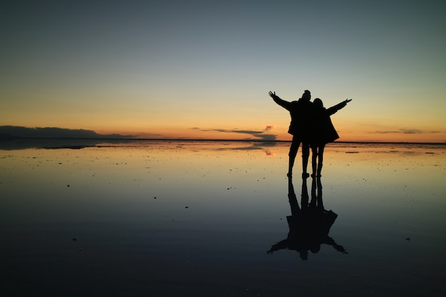 Silhouette of a couple on the incredible mirror effect of uyuni salt flats, bolivia