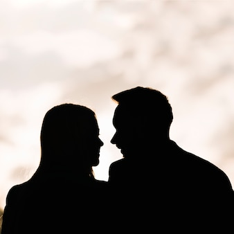 Silhouette of couple looking at each other against sky