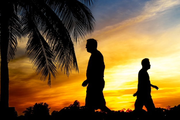 Silhouette of couple men riding bicycle at sunset