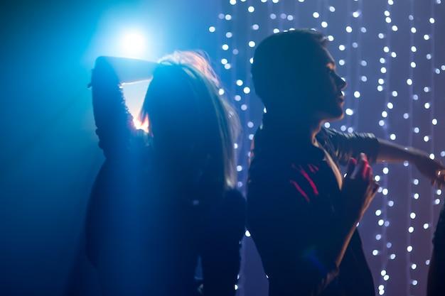 파티에서 나이트클럽에서 춤을 추고 즐거운 시간을 보내는 사랑하는 젊은 남녀의 실루엣 커플