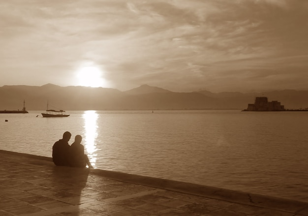 Silhouette of a couple on the seaside promenade at sunset in sepia tone