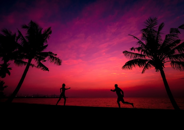 Silhouette of couple on tropical beach during sunset on background of palms