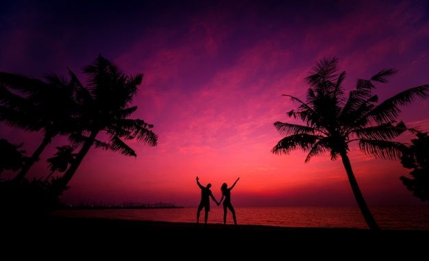 Silhouette of couple on tropical beach during sunset on background