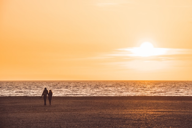 Silhouette of couple walking on the beach at sunset, almeria, spain