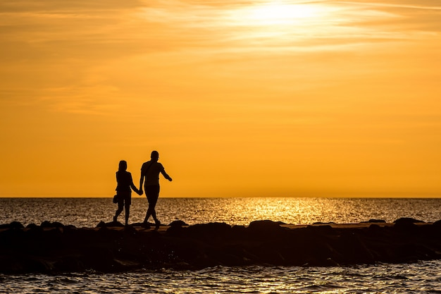 Silhouette of couple walking on the pier during the golden hour of sunset