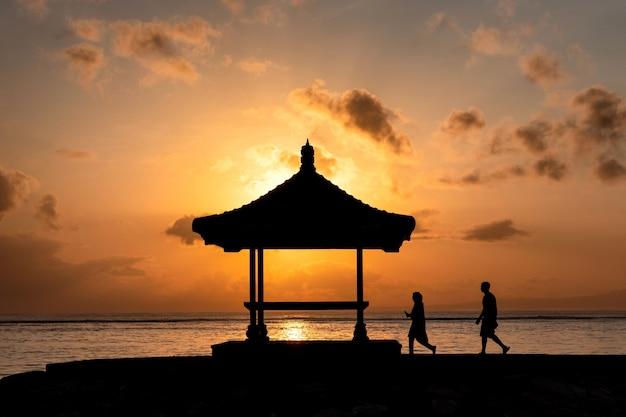 Силуэт пары, идущей в павильон с восходом солнца, сияющим на береговой линии