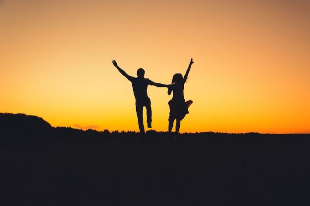シルエットのカップルは、夏のオレンジ色の夕日を背景に楽しくジャンプしています