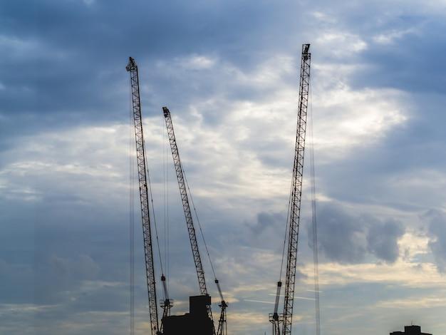 Silhouette crane at building construction site.