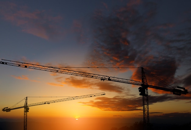 Silhouette of crane construction building towers at sunset.