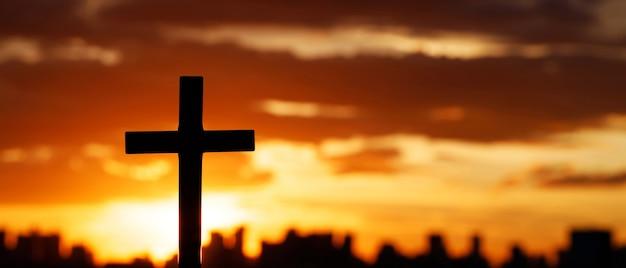 夕暮れ時の空を背景にシルエットをクロスします。宗教の概念。
