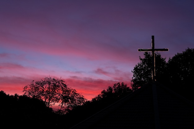 Silhouette cross on church roof with dramatic sky at dawn.