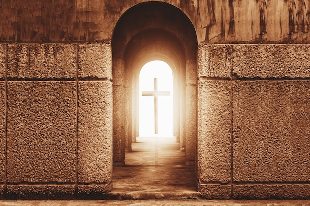 Silhouette of the cross at the end of tunnel with ray of sunlight behind
