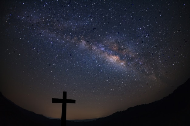 Silhouette of cross over milky way background