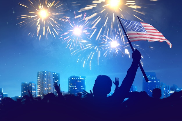 Silhouette of crowd people holding an american flag with fireworks and night scene view. fourth of july concept