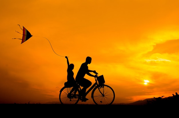 Silhouette cycling brother and sister with kite.