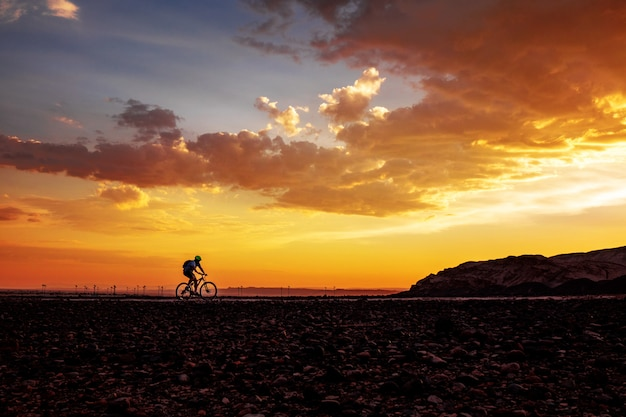 Silhouette of cycling man on bike on beautiful sunset background