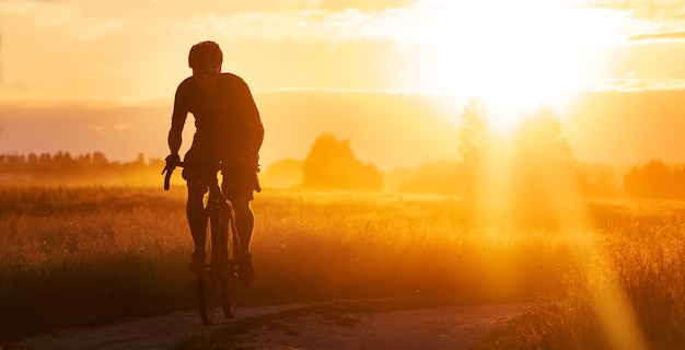 Silhouette of a cyclist on a gravel bike riding a trail in a field on a dramatic sunset