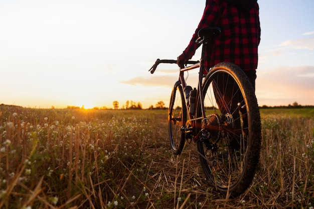 Silhouette of a cyclist and his bike against the sunset sky background.