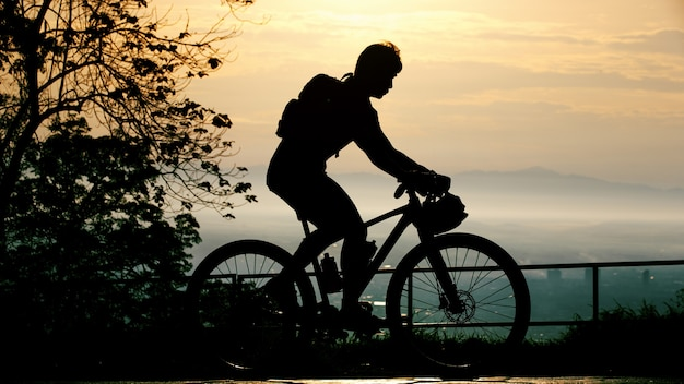 Silhouette of cyclist on mountainbiker at sunset
