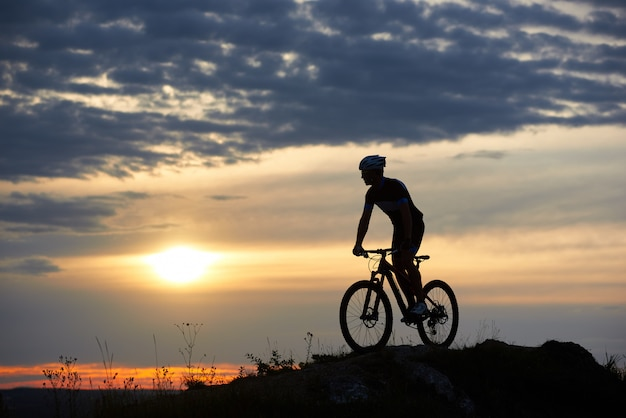 Silhouette of cyclist standing on bicycle