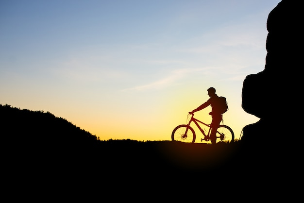 Silhouette of cyclist with bike on the rocks at sunset.