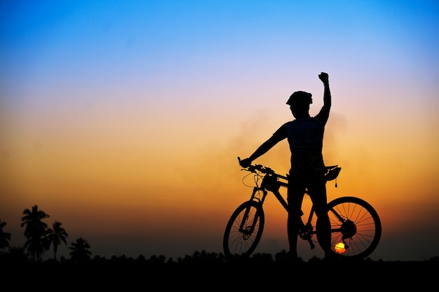 Silhouette of cyclist with mountain bike on beautiful sunset time.