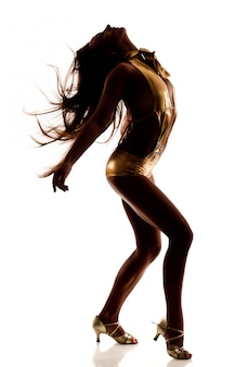 Silhouette of dancing slim beautiful woman in sexy golden costume and medium heels shoes isolated over white wall