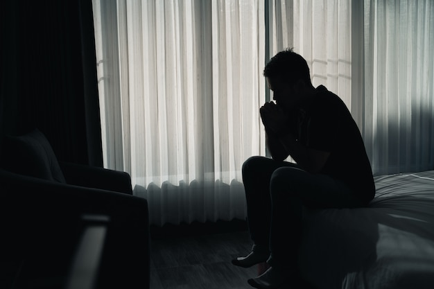 悲しいことに寝室のベッドに座っているシルエットうつ病の男性、うつ病の概念