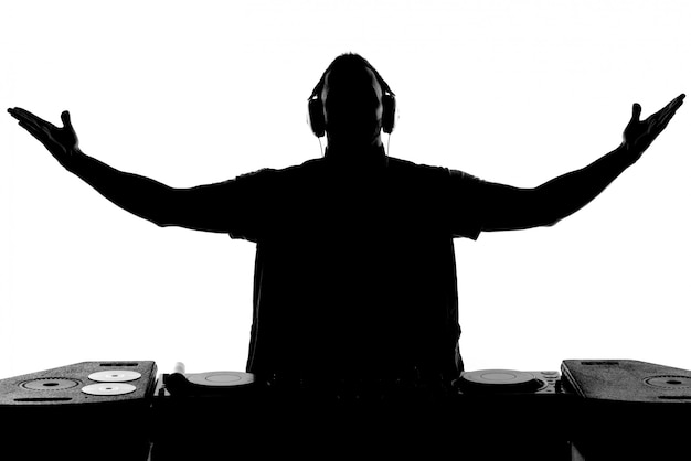 Silhouette of dj gesturing and spinning on turntable.