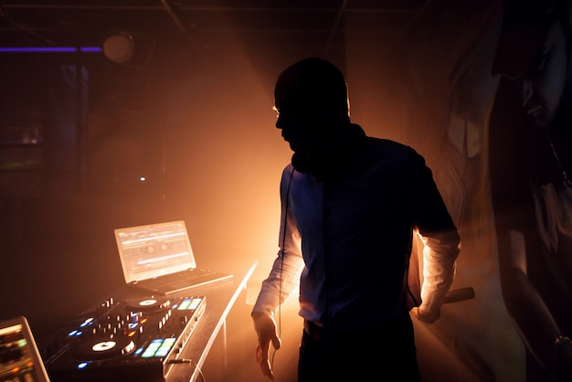 Silhouette of a dj with a microphone at the mixer on the nightclub