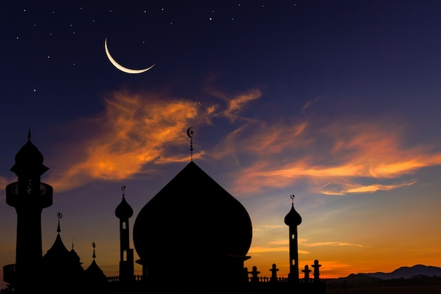 Silhouette dome mosques on dusk sky and crescent moon