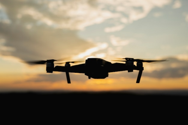 Silhouette of a drone flying at sunset
