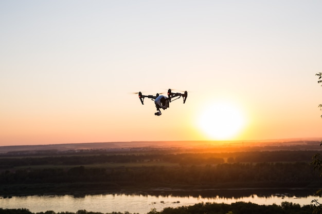 Silhouette of drone, quadrocopter with photo camera flying in the sky.