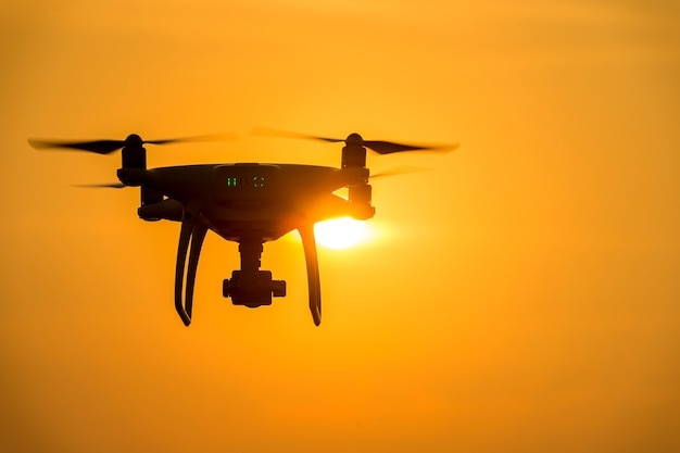 Silhouette drone with camera flying at sunset.