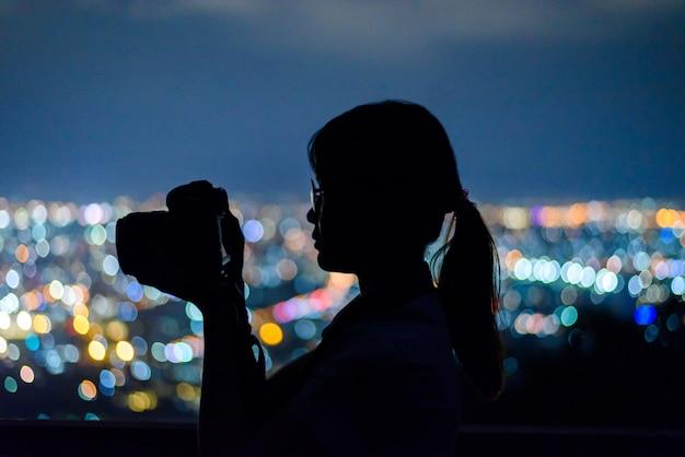 Silhouette женщина фотографируя с камерой dslr на ноче в таиланде.
