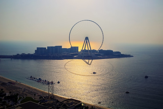 Silhouette of dubai eye ferris wheel at sunset with warm reflection on sea surface