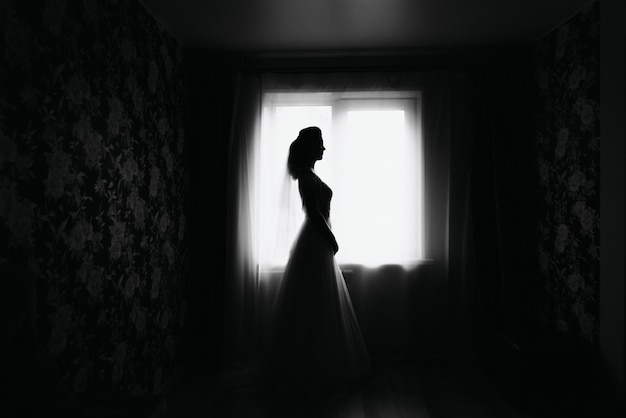 Silhouette of an elegant bride in a dress by the window on the wedding day