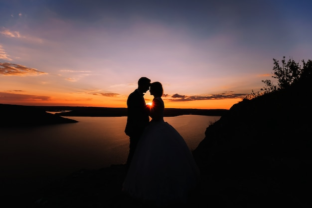 Silhouette of embracing groom and bride.