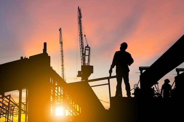 Silhouette of engineer and worker on building site, construction site at sunset in evening time