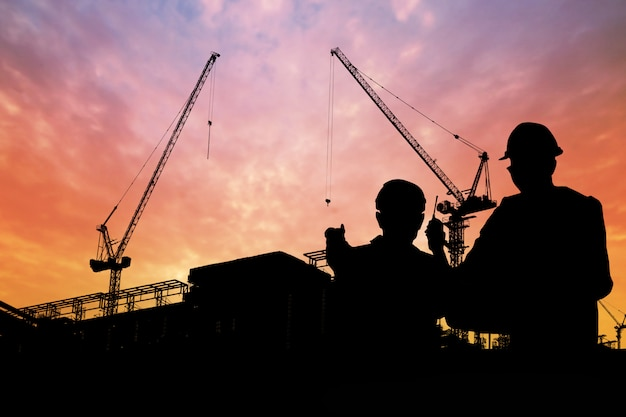 Silhouette of engineers with worker in construction building