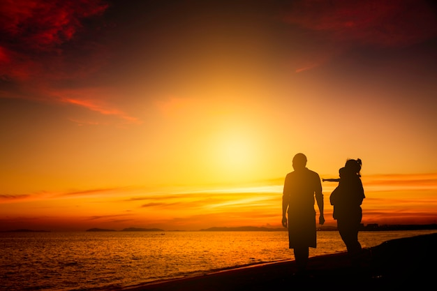 Silhouette family happy on the beach in sunrise or sunset. freedom life and well being concept