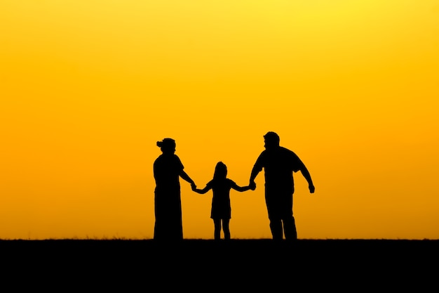 Silhouette of a family walking in sunset